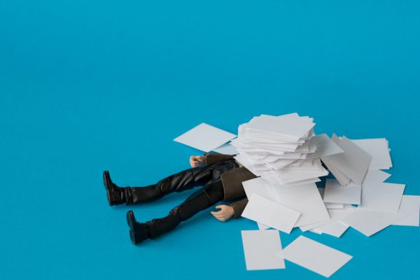 figure on fall under pile of paperwork